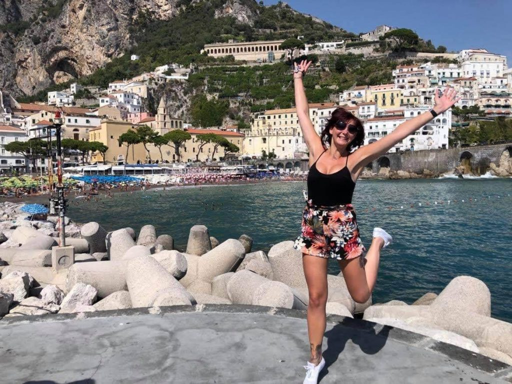 Amalfi Coast Road Trip - girl jumping in the air with the back drop of the amalfi coast iconic houses
