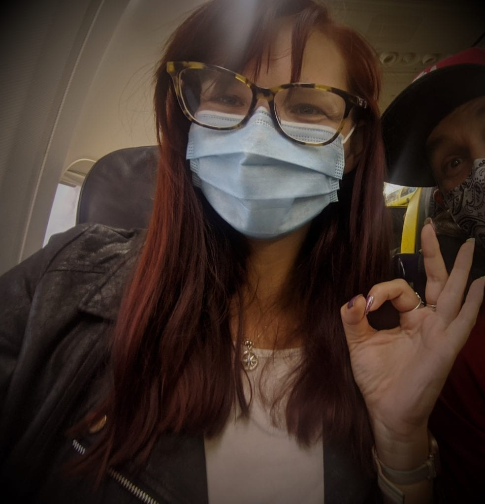 Travel tips and advice through Covid 19 - female blogger on a ryanair flight wearing a surgical mask making the ok sign as she's ready to depart on another holiday