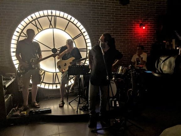 Malta and Gozo Island - Rock Band playing on stage in front of a large lit up victorian clock face
