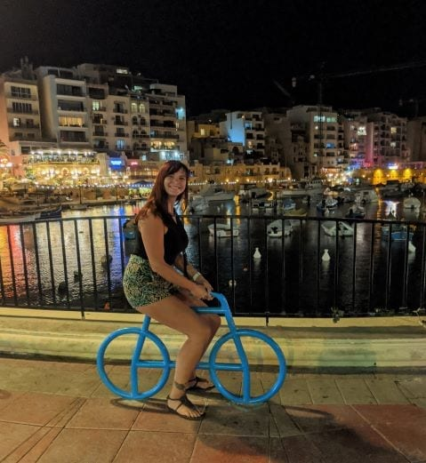 Malta and Gozo Island - woman on a metal statue of a bike in front of the bay in St Julians