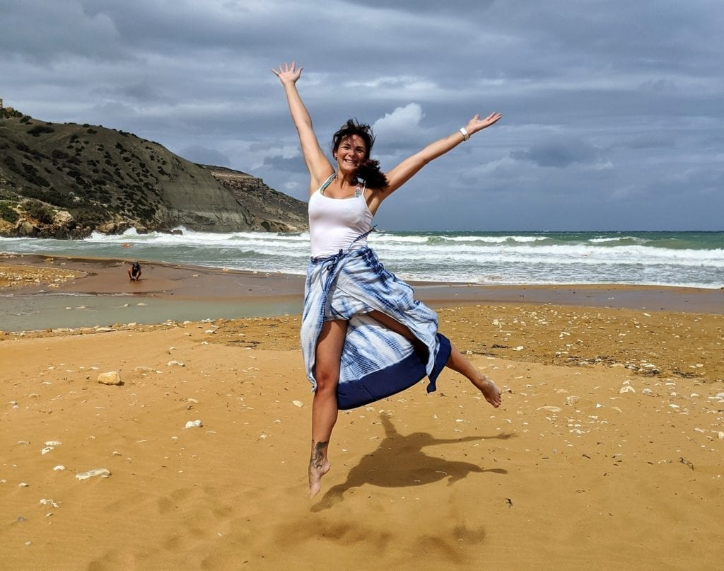 Malta and Gozo Island - young woman jumping on the sand on the beach in Gozo