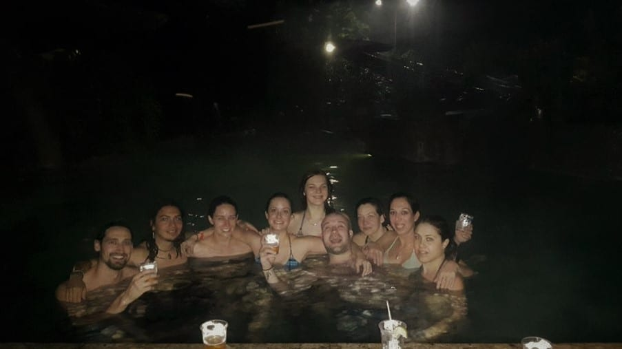 Things to do in Arenal Costa Rica -  A group of young people enjoying drinks in the natural hot springs at night