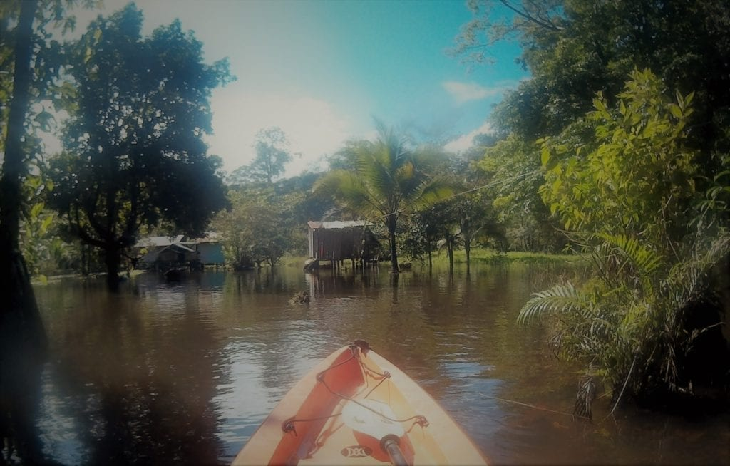 Top adventurous things to do in Costa Rica - tip of a kayak as it appraches a wooden jungle cabin