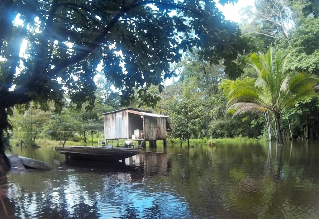 Top adventurous things to do in Costa Rica - a wooden shack at the edge of a narrow canal in the jungle