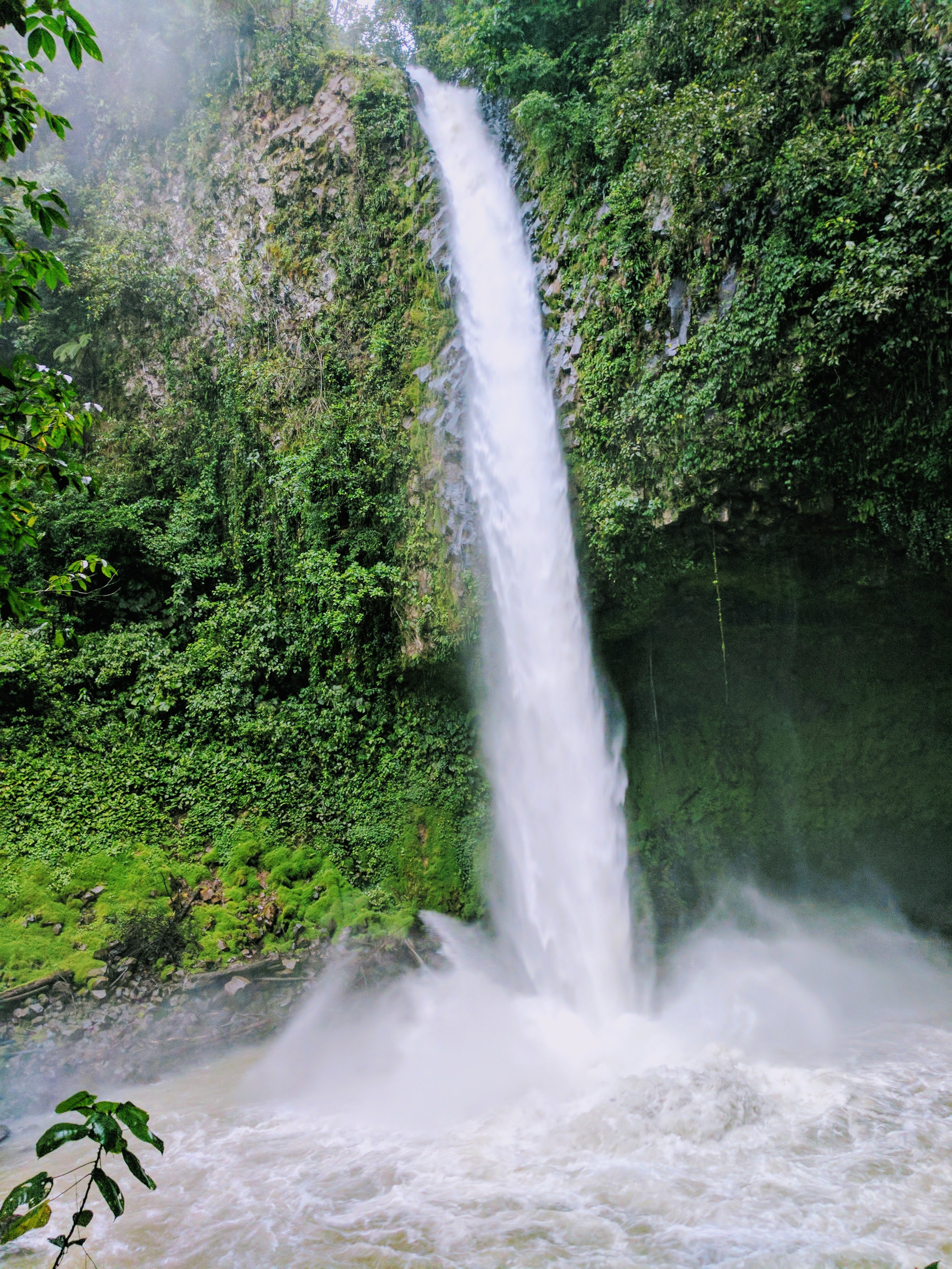 Things to do in Arenal - view at the bottom of a tall waterfall