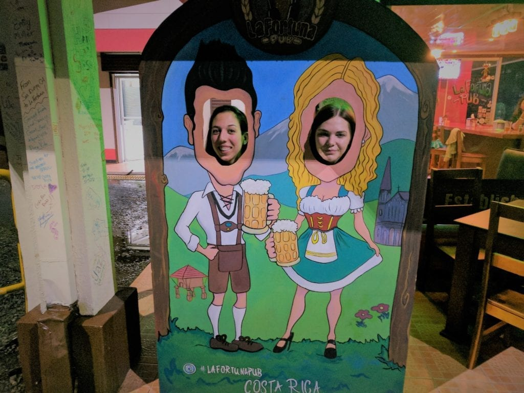 Things to do in Arenal - two women with their heads through a picture making it look like they are in traditional german outfits drinking steins