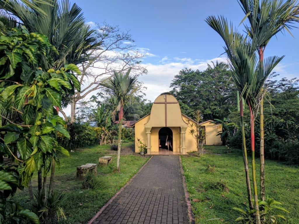 Costa Rica Itinerary - yellow chapel surrounded by palm trees in Tortuguero village