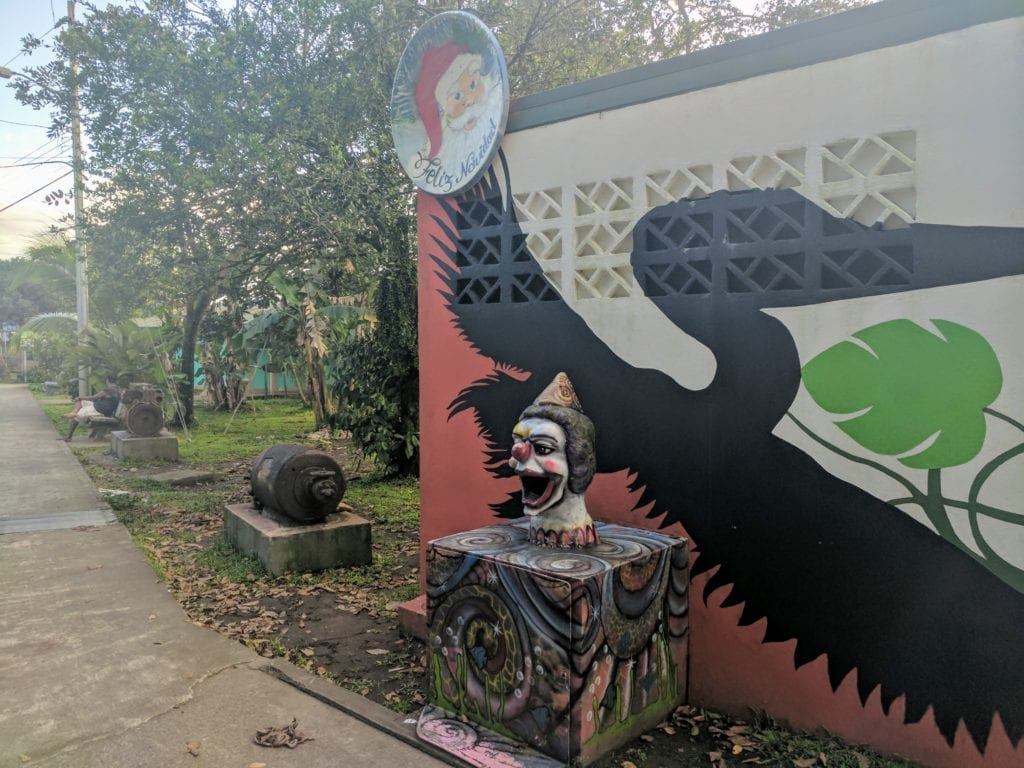 Costa Rica Itinerary - statue of a clown face against a colourful wall