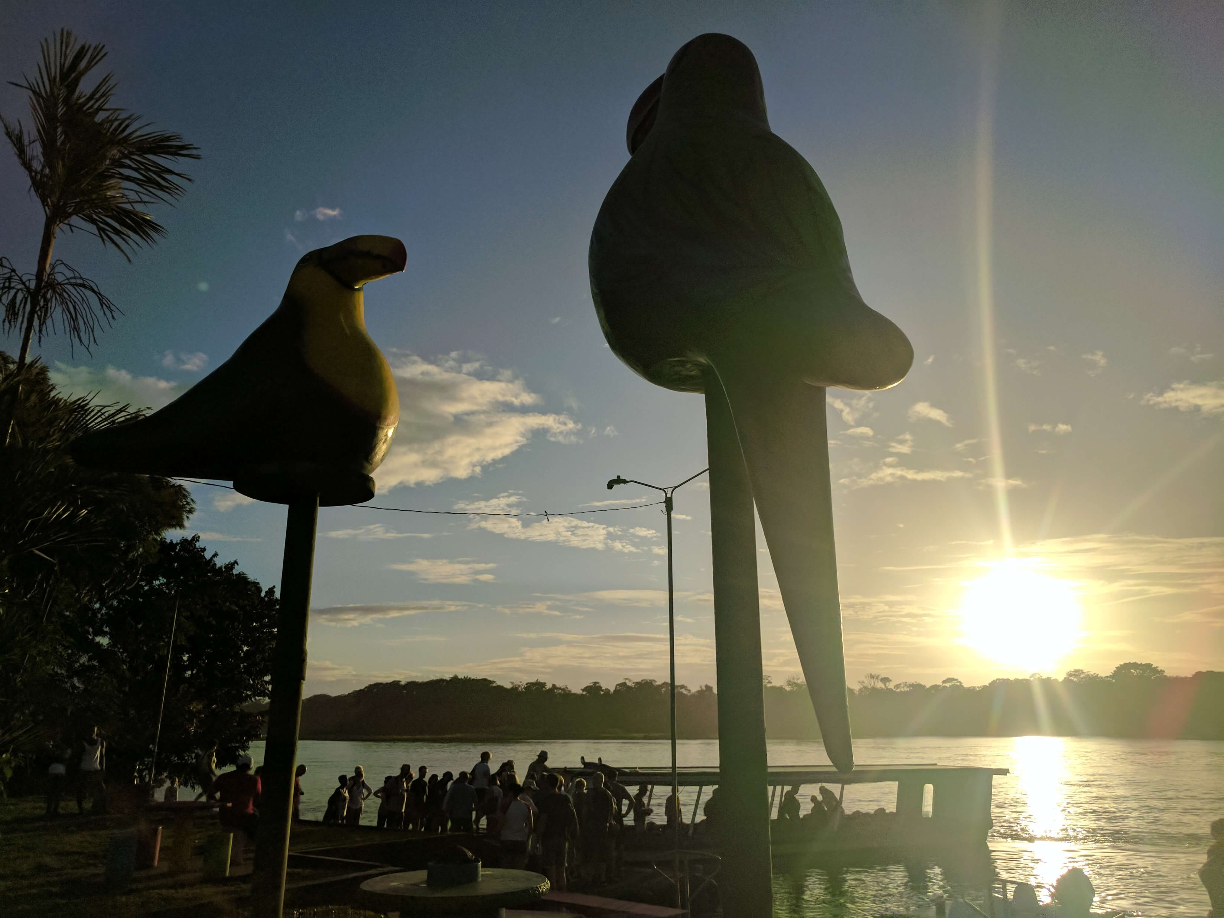 Costa Rica Itinerary - the sun setting on Tortugero village through the large statutes of tropical birds