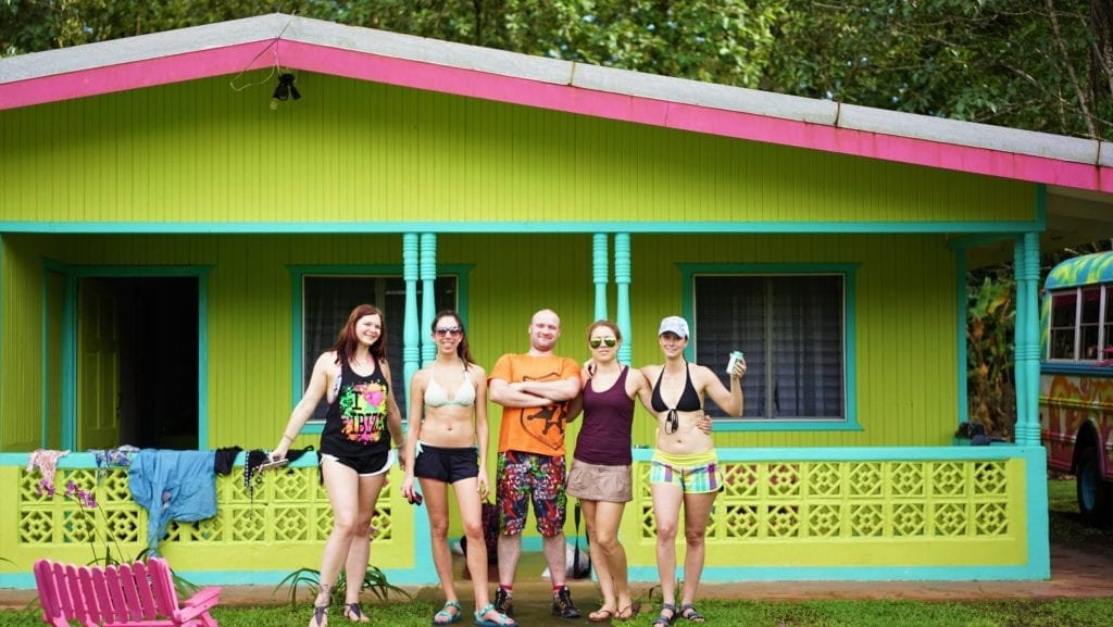 Pros and Cons of Group Tours - group of travellers looking happy outside a lime green and turquoise cabin