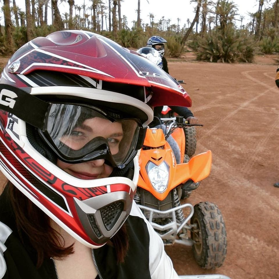 Epic things to do in Marrakech - girl smiling with helmet on a quad bike in the palm coves of Marrakech