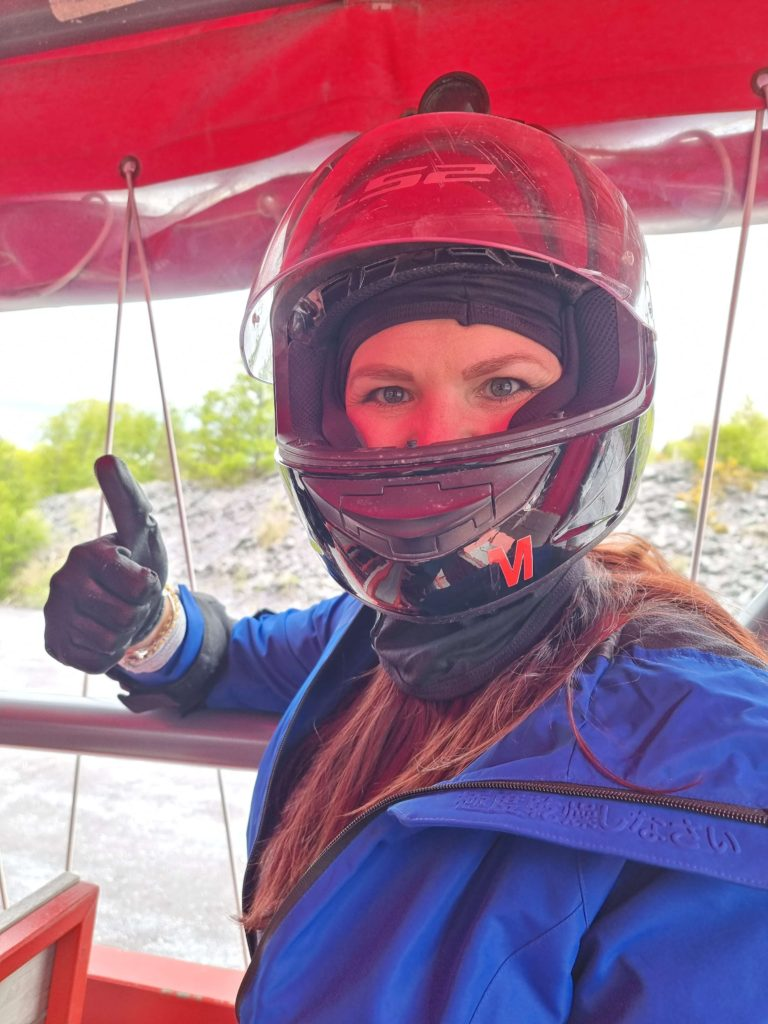 Zip World Karts - a woman with a crash helmet on giving the thumbs up on the ride up the quarry to go go-karting