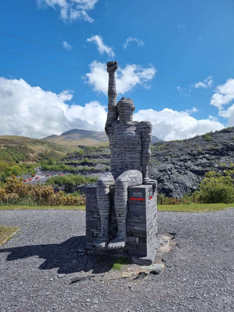 Zip World Karts - a statue set against the welsh slate mountains with a single arm in the air