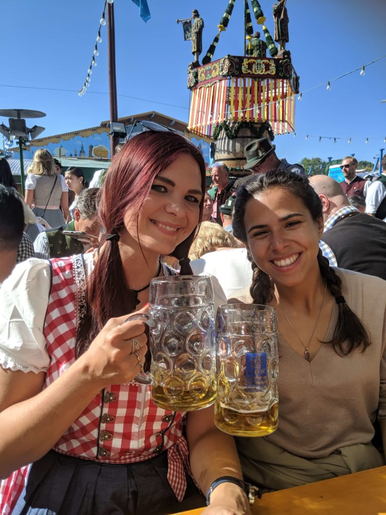 Munich beer festival - beer tent with women drinking steins and wearing Dirndl